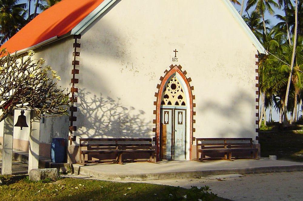 Porche de l'église de Raroia avec la pierre du marae